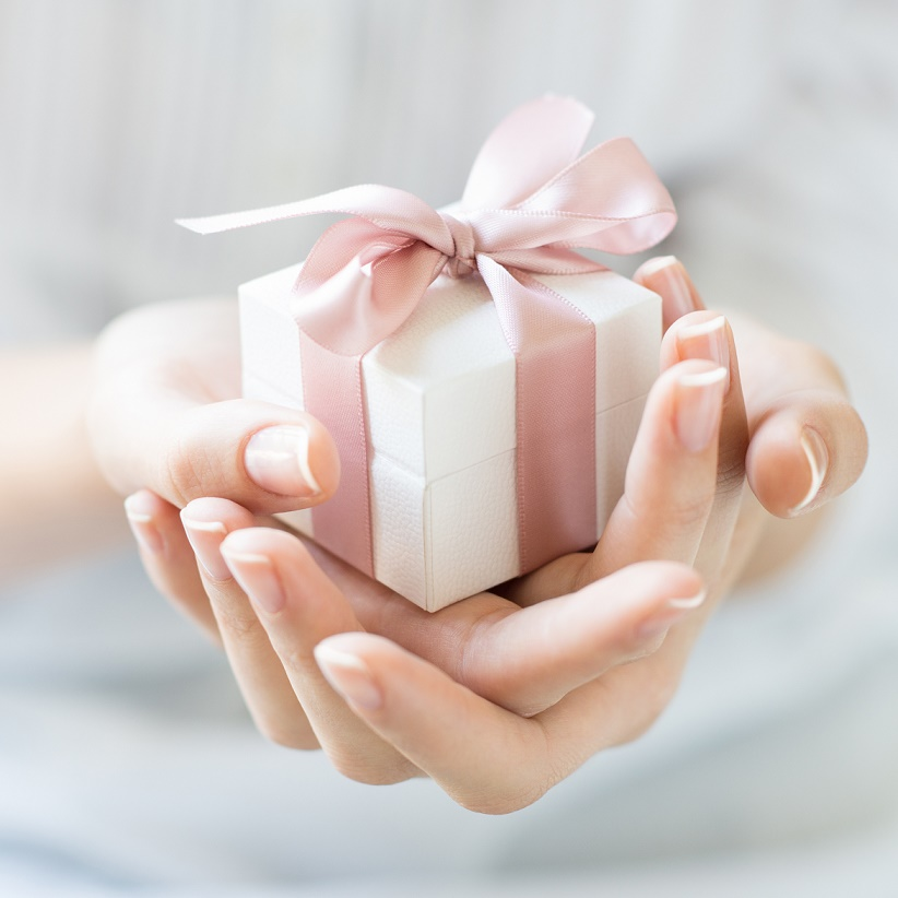 Close up shot of female hands holding a small gift wrapped with